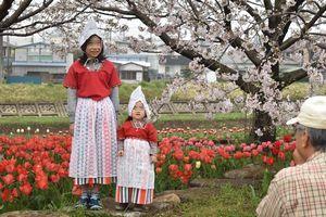 チューリップ花壇の前でオランダ民族衣装を着て笑顔を浮かべる女の子達